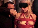 Samantha, a blonde chick, arrives at the dungeon where shes met by Mistress Stefani and Master Rick. Shes new to it all, so they give instructions.  She's shackled and lashed.  Then, they tie her up with ropes, and her tits are tortured with a pair of tongs.
