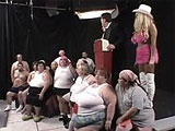 This is part 2 of the 300lb gangbang.The participants are all grouping up and having sex with each other and the fluffers before the main event.