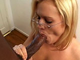 Erika Kole, a cute blonde with glasses, smokes a black cock.  She gags a few times, and then gets a lovely facial all over her specs.