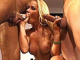 Jodie Moore, a hot blonde, is getting piped by two big fat cocks. After she hogs on both guy's cocks, she gets fucked in her ass and cunt before taking a big dual facial.