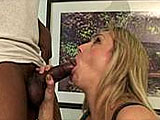 This gorgeous blonde milf welcomes a black guy's hard erection deep inside of her mouth. Check out how her tongue smothers his ball sack while her hand jerks his shaft. She moans the entire time he's fucking her mouth.  Then, he releases a load onto her beautiful boobies.