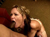 A black guy leans back on the couch as a busty milf, Kelly Leigh, sucks his dick and licks his balls. Watch how she continues to throat every inch as she slips out her top. When he's ready to cum, the whore stops and pulls off. She opens her mouth wide so the guy can blast her face with cum.