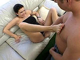 Chloe, a hot busty brunette, is giving Mark Wood's big johnson some good foot play. She gets much enjoyment out of running his hard cock between the soles of her feet.