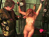 A pretty little blonde named Kristi gets violated.  An older dude makes her lick his riding crop, then he puts rubber bands around her tits. The suspension cuffs are brought out, and soon Kristi's hands are tied behind her head.  After clipping clothespins around her breasts, the old guy spanks he