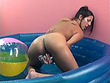In this scene, Lavender is playing in a kiddie pool in the middle of a room.  She strips out of her bikini and shoves glass dildos in her pierced and shaved pussy.