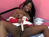 In this scene, ebony Liani is dressed in her Mrs. Claus outfit.  She masturbates and shoves a vibrator in and out of her shaved black pussy.  