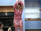 In this scene, Mariah is naked and holding on to a steel girder above her head.  Brooke is wrapping her in red plastic wrap.  When she is fully encapsulated in plastic, Brooke pokes a hole in the plastic so she can get at Mariah's pussy.  Brooke tries to stuff a dildo in Mariah's tight hole.