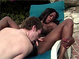 This scene features Kimber Blake.  This ebony starlet gets with a white guy outside by the pool, slurping on his Johnson, and then getting her shaved snatch licked.  She takes it it the vag and her bunghole before getting cum blasted on her round brown booty.
