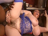 In this scene, BBW Kitty Lee is on the couch shoving a dildo in and out of her hairy pussy.  Two black guys join her and immediately go after her volleyball sized tits.  She sucks their cocks and then they take turns fucking her.  First they hit her pussy; then her ass.  They give her a DP dicking a