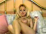 Stacy Burke is the big tittied blonde for this scene.  Watch her strip and tease on the bed, pulling out her set of big cans.  Then watch her rub that pussy like she's polishing silver.