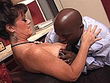 In this scene, a young (and possibly retarded) black guy gets a sex-ed lesson from Miss DeBella.  She starts out by giving him a blowjob and then he licks her wrinkled tits and pussy.  He fucks her fast and hard on the couch, and blows his load in her mouth and on her chin.