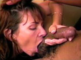 A gorgeous brunette grinds her face up and down on a big black cock.  The guy's pulsating boner blows cream all over her skillful mouth.