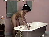 This is a compilation of two bathtub scenes. The first girl cleans up with soap and then sits on the side of the tub, ramming her bushy snatch over and over with a dildo. The next scene is an even hotter brunette, who runs a bubble bath and gets in with her rubber duckie. Being such a naughty girl,