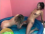 In this scene, these two amateur girls fuck around together in a kiddy pool.  They kiss, lick each other's tits, and eat pussy.