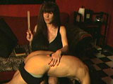 In this scene, a mistress dominates her submissive by spanking his ass with a ruler and then smothering his face with her wet pussy.  She has him worship her stockinged feet and be her ashtray as she smokes a cigarette.