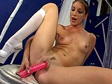 In this scene, Brandi Lyons is sitting on a stool wearing nothing but high heels and white knee-high socks.  She is suggestively sucking on her pink dildo and rubbing it on her tits and pussy.  She shoves it in and out of her box, keeping it lubed with her mouth.  She abandons the dildo and finger b