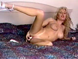 In this scene, a busty blonde puts a show in the bedroom.  She strips down naked to show off her boobs and body, rubbing lotion all over herself.  A vibrator is introducedand she works it in and out of her pink pleasure pocket.