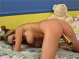 In this scene, a sexy little blonde with big tits plays by herself on her bed.  She rubs a vibrator between her perfect tits and then works it on her clit and pink hole.  This perky teen gets herself off and is all smiles.