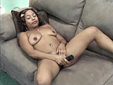 In this amateur video, Stephanie is by herself on the couch.  She sucks on her big black dildo to lube it up, and they stuffs it inside her shaved snatch.  Stephanie moves to the floor and creams all over the toy some more.