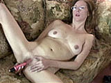 This scene has amateur girl Elise by herself on the couch.  She pulls off her sweater to reveal her pierced tits, and then peels off her jeans so she can get at her pussy.  After fingering her slit, she works a vibrator around and in her hole.  Elise works it until her orgasm pushes the toy out.