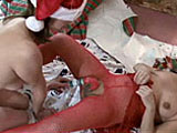 This scene has amateur girl Elise wrapped up in Christmas paper.  She is a gift for Vixen the midget.  Vixen un-wraps her gift to revel a set of natural, pierced tits.  Elise lays on the floor, where Vixen proceeds to stuff a candy cane up her cooter.  Vixen gets the favor returned as they continue