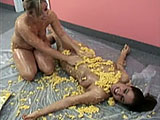 Lily and Rena Lynn are hungry so they baked up some mac and cheese. But when they get naked, they realize that spreading the warm, gooey noodles on each other's bare tits is more fun than eating it. They smear and play and even nibble on some of the cheesy goodness and then press their mac and che