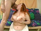 A not so skinny redhead is getting her massive fun bags fucked by a big cock.   She alternates between sandwiching the dude's cock between huge melons and mouth fucking him before having her chubby face showed large amount cum.