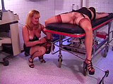 One woman is in the submissive role with another woman giving a pain lesson. After some hard spanks, she opens her legs and cuffs her ankles to a spreader bar.  The submissive's labia are spread wide with forceps and a massive violet wand is used on her.  She then clips her lips with eight clothespi