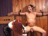 Mistress Scarlette is giving her new slave a lesson in pain.  Once he's strapped into her torture chair, she can show him what real pain is.